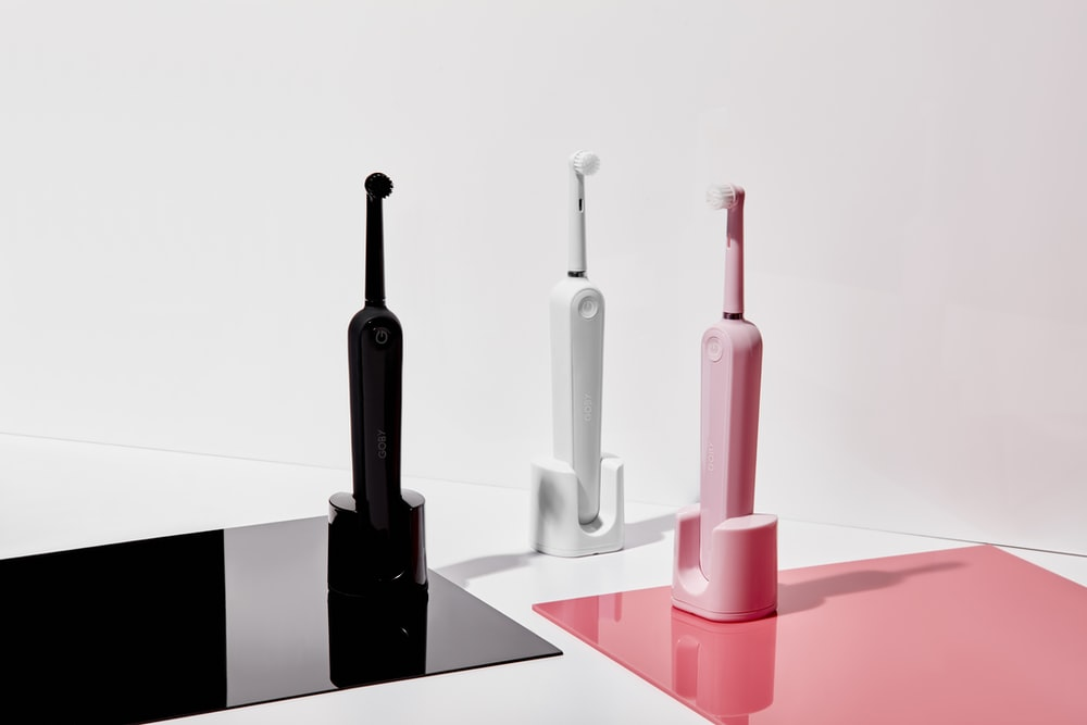 three assorted-color electric toothbrushes