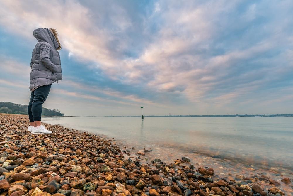 woman standing beside seashore during daytime