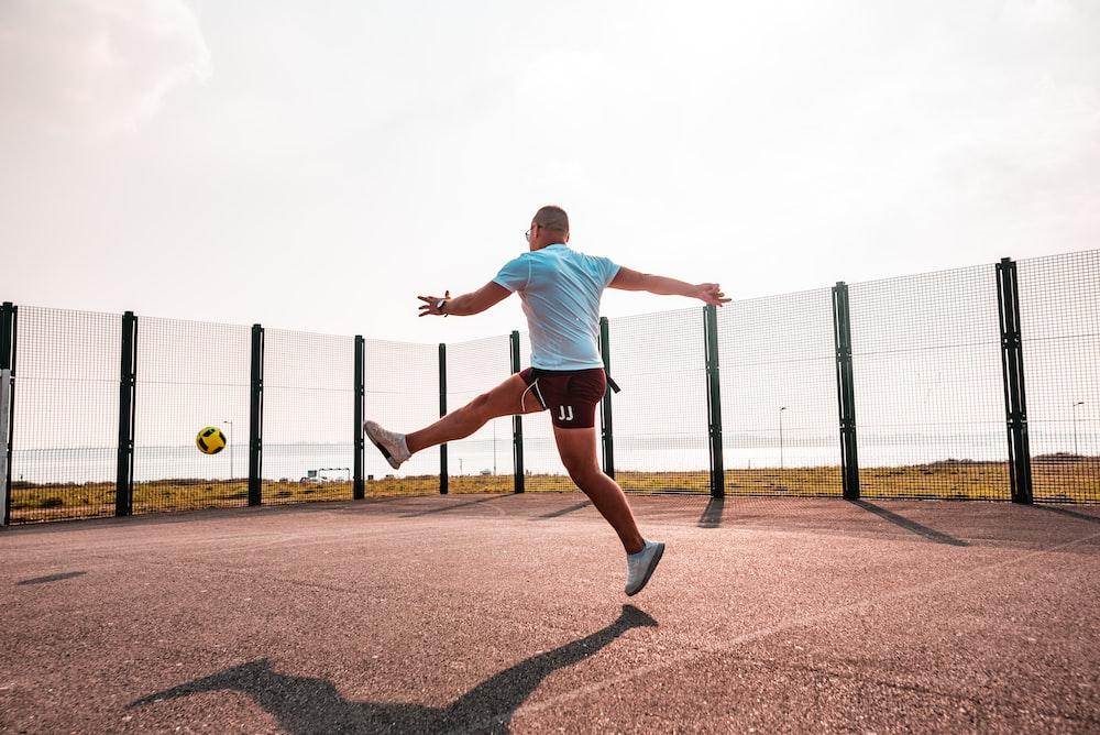 man kicking the yellow ball during daytime
