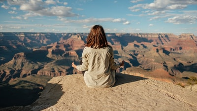 woman sitting on hill grand canyon zoom background