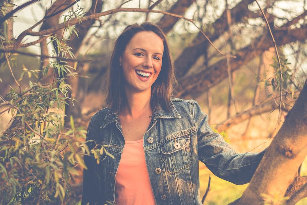 woman wearing blue denim jacket behind of tree
