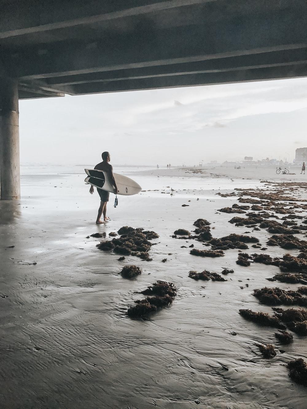 man walking on sea carrying surfboard