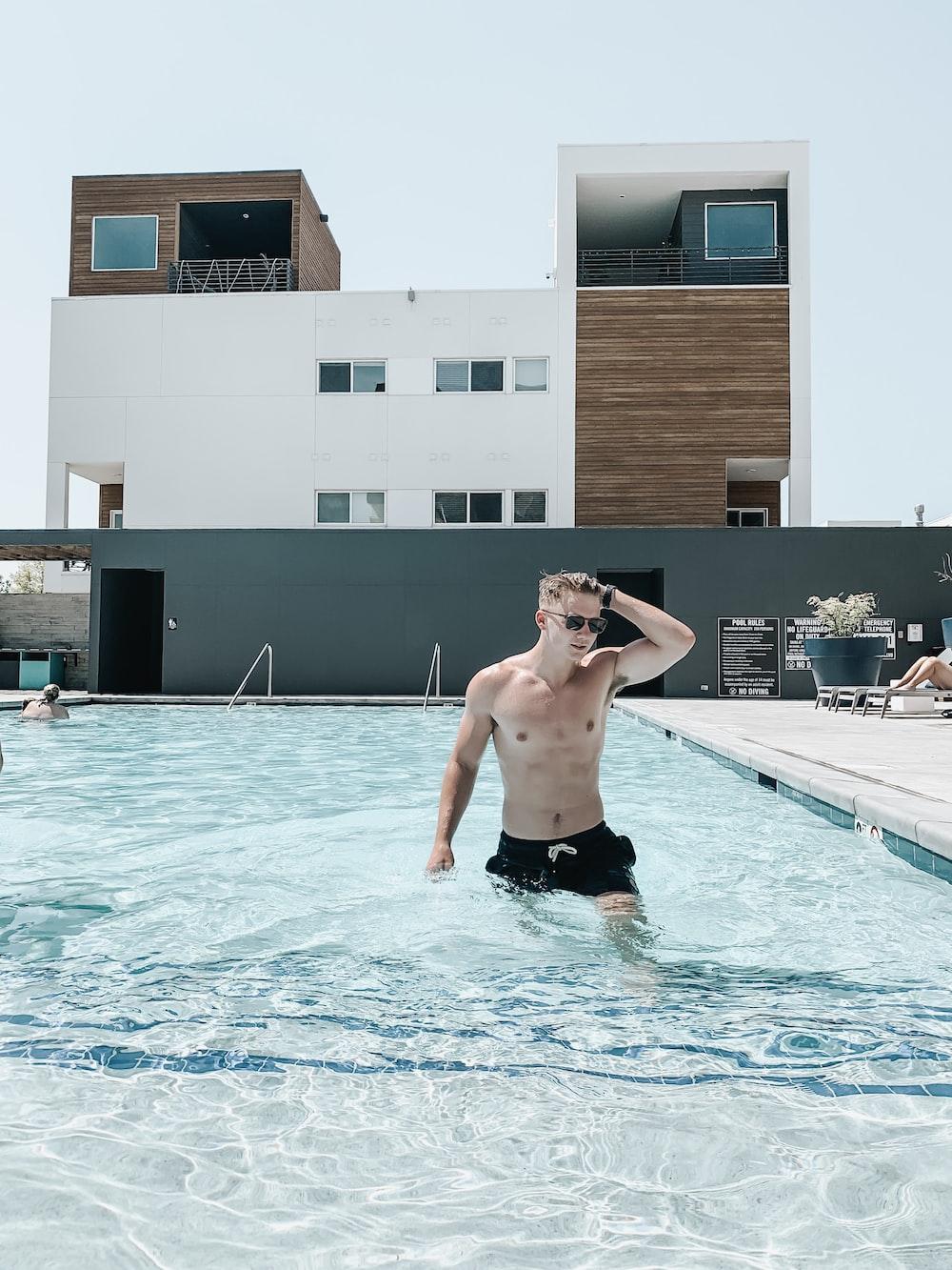 man swimming on swimming pool during daytime