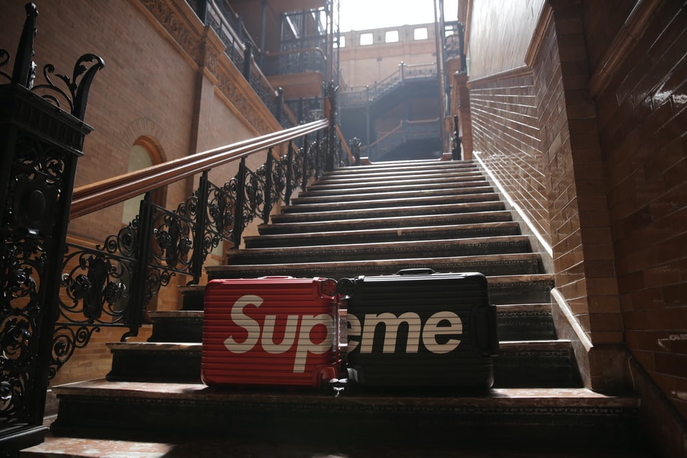 two black and red Supreme hard-case luggages