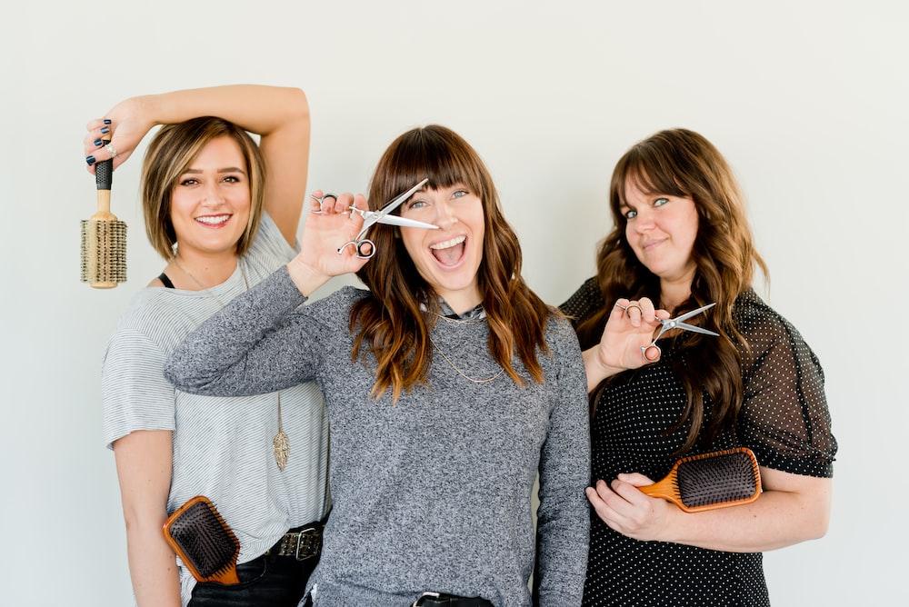 three women holding scissors and brush