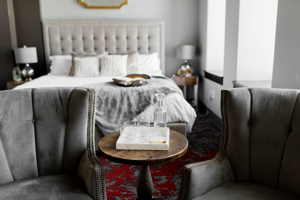 white hardbound book on table in between grey wing chair