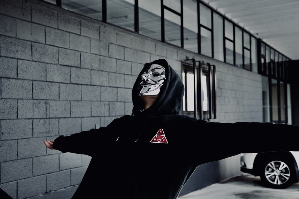 person wearing Guy Fawkes mask opening his arms