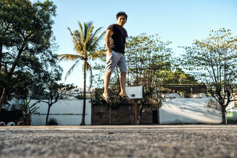 low angle photo of man standing on concrete ground beside trees