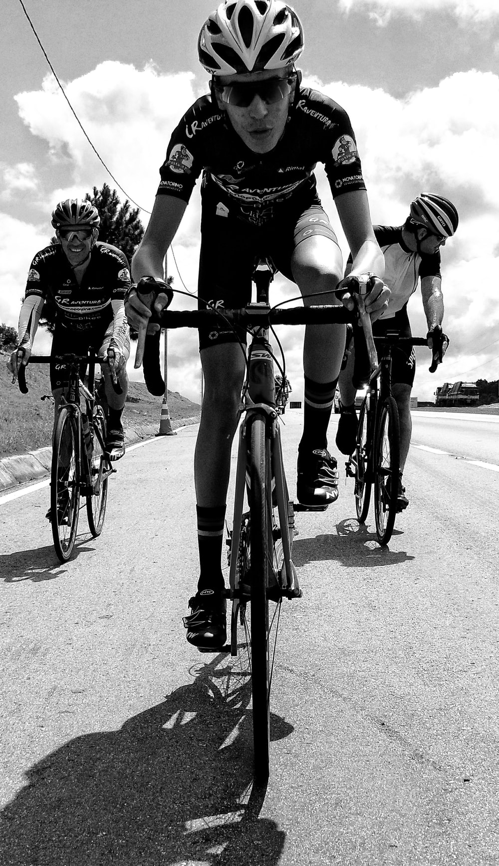 grayscale photography of unknown persons driving bicycle outdoors