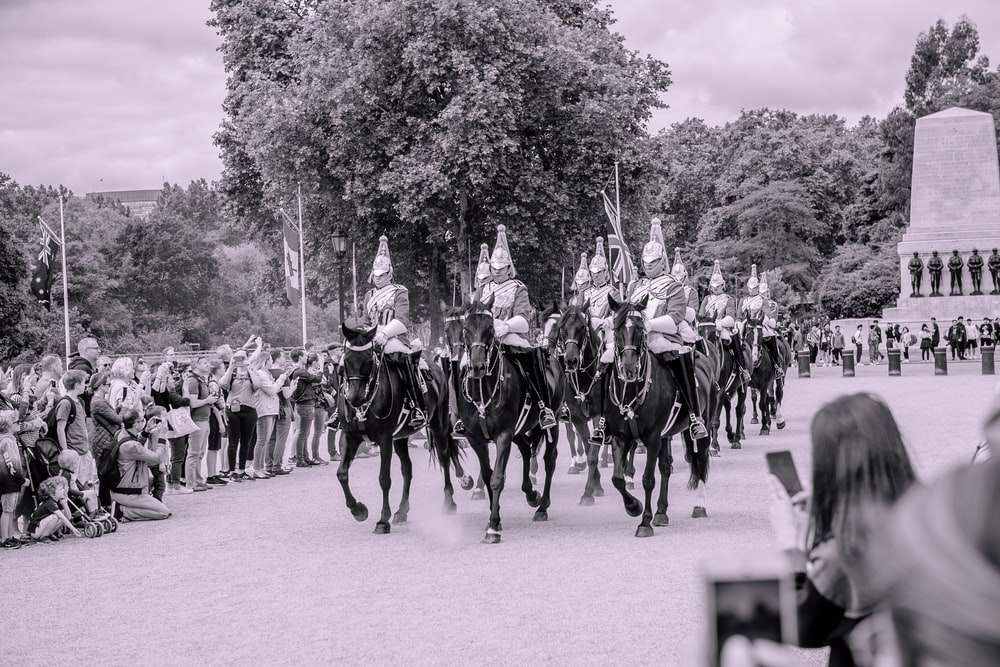 grayscale photography of knights riding on horses