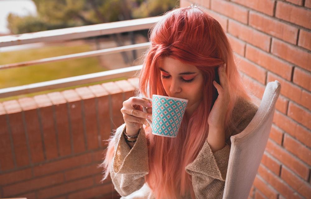 woman wearing beige trench coat holding teal ceramic mug