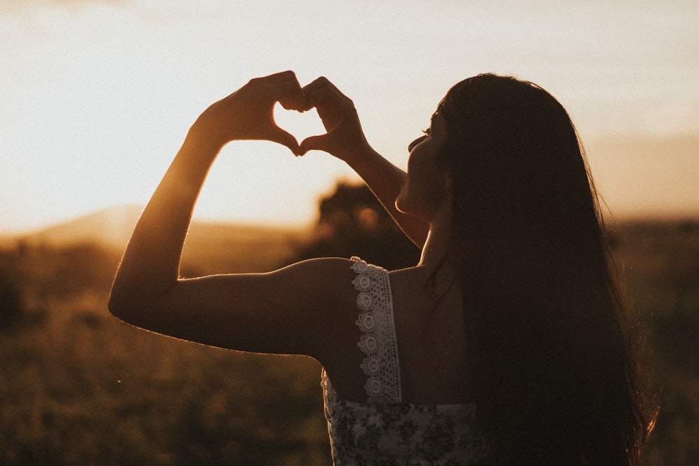 woman forming heart with her both hands