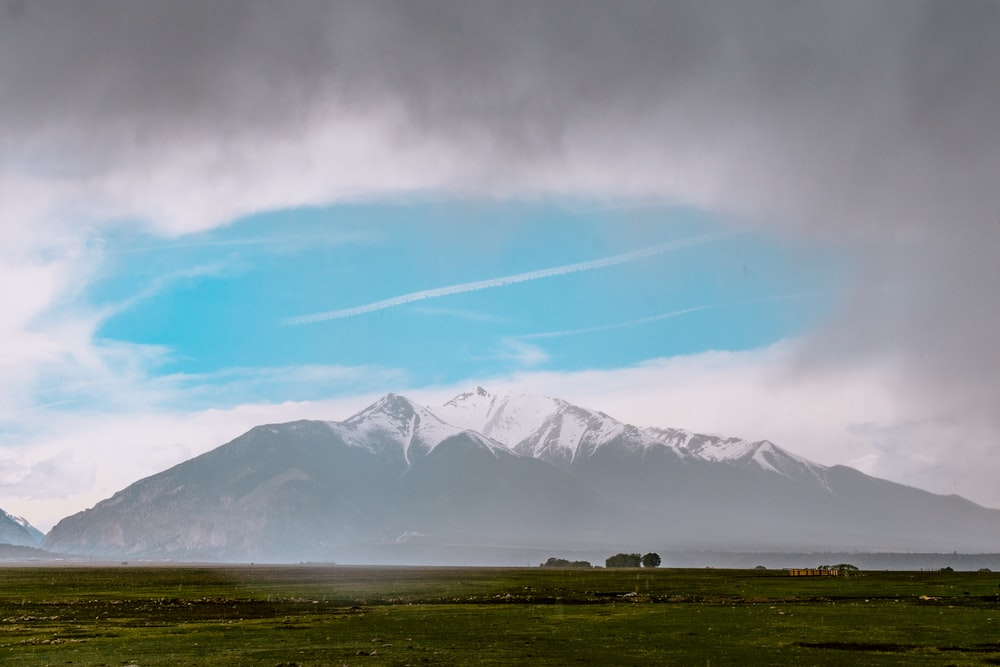 snow-covered mountain under cloudy sky