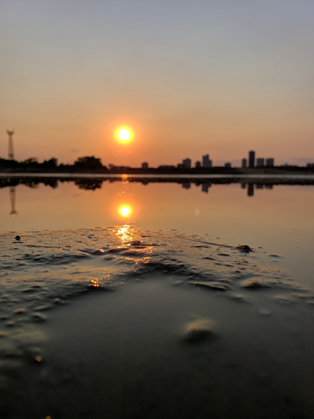 sunrise at the city through body of water