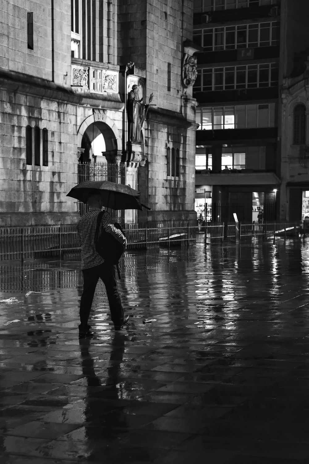 person walking and using umbrella near buildings