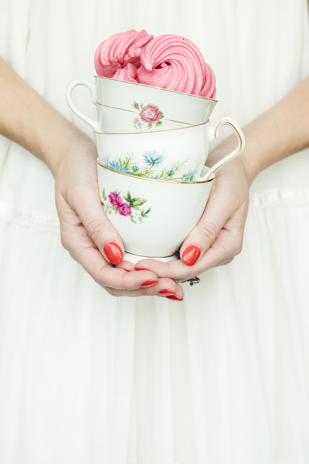person holding three floral ceramic teacup