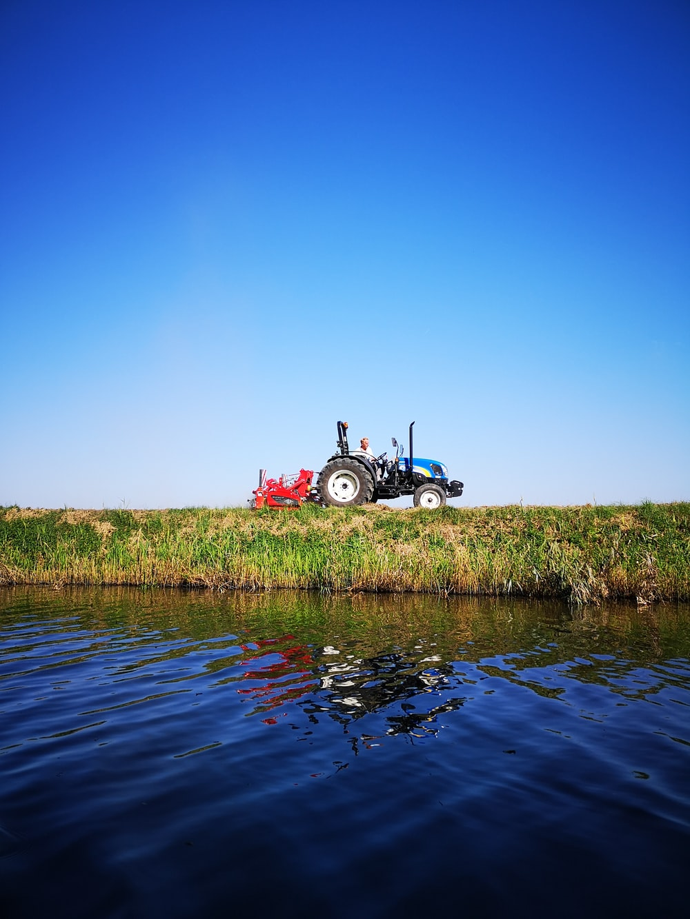 blue and black tractor near body of water