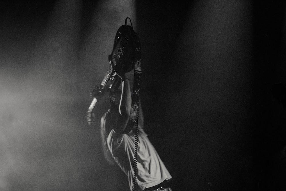 man lifting his electric guitar