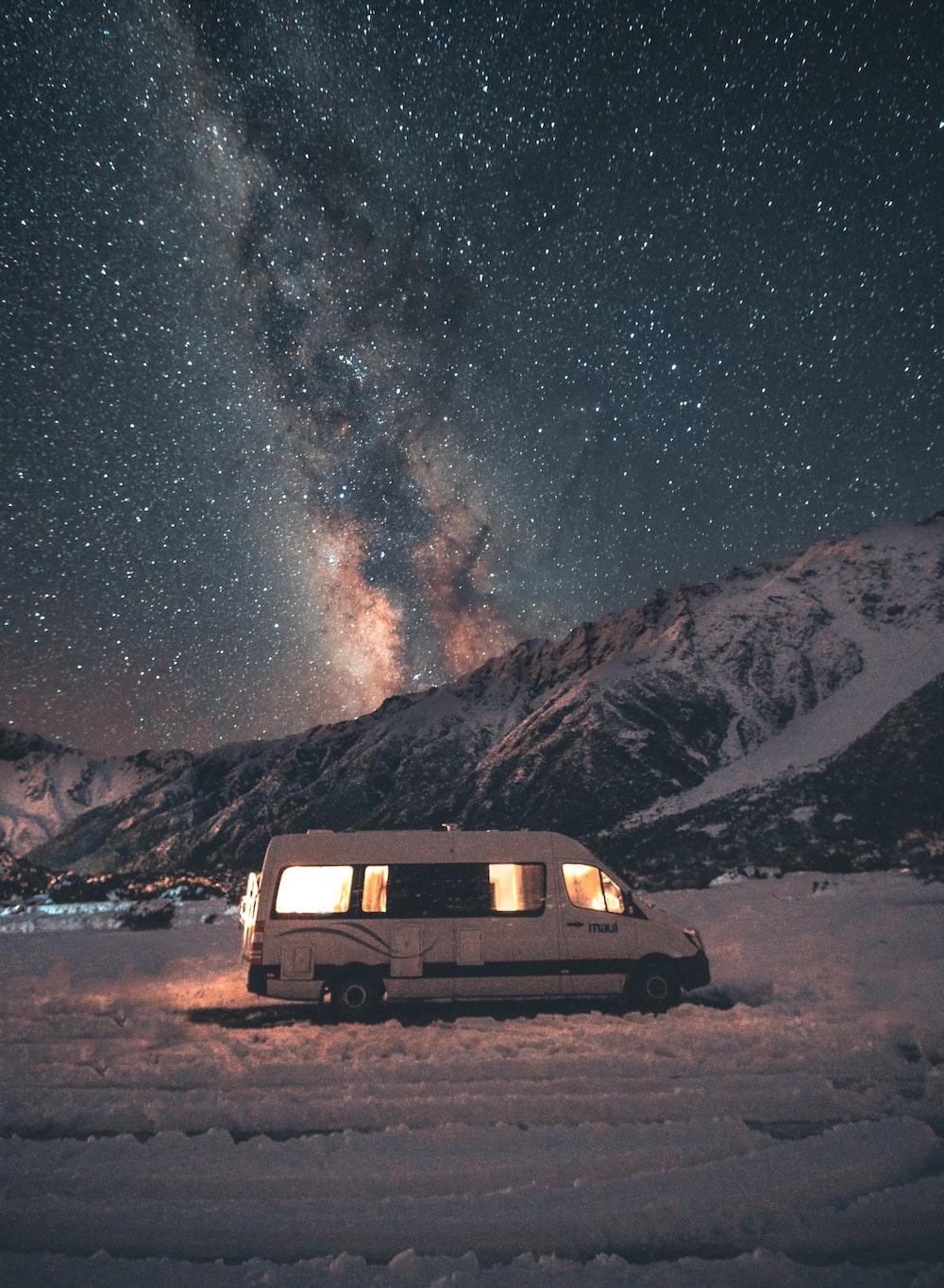 white minivan parked on snow during nighttime
