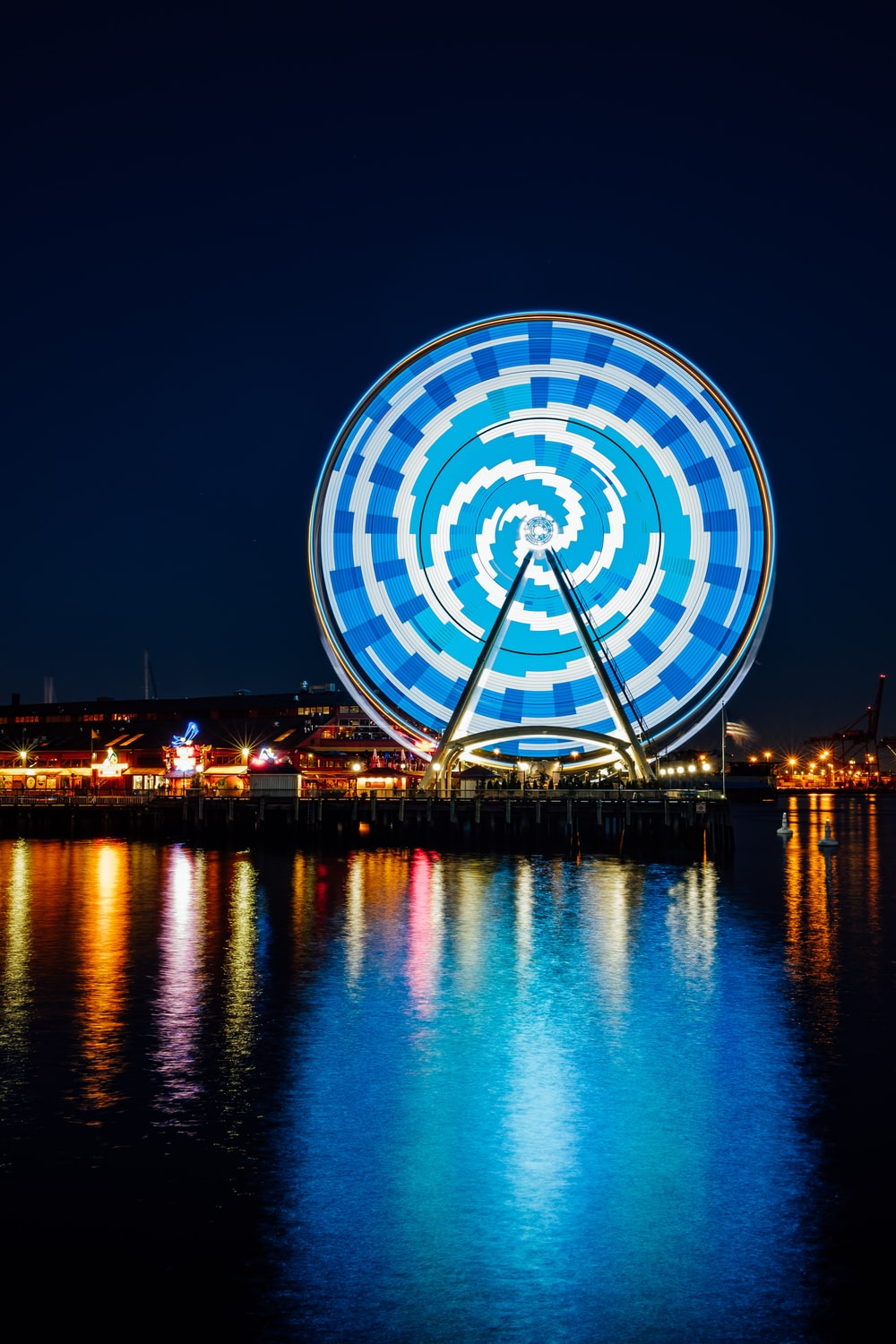 Ferris Wheel with blue LED light reflecting on body of water during night