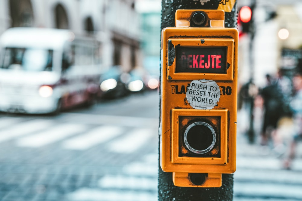 push to rest the world sticker on yellow pedestrian light switch