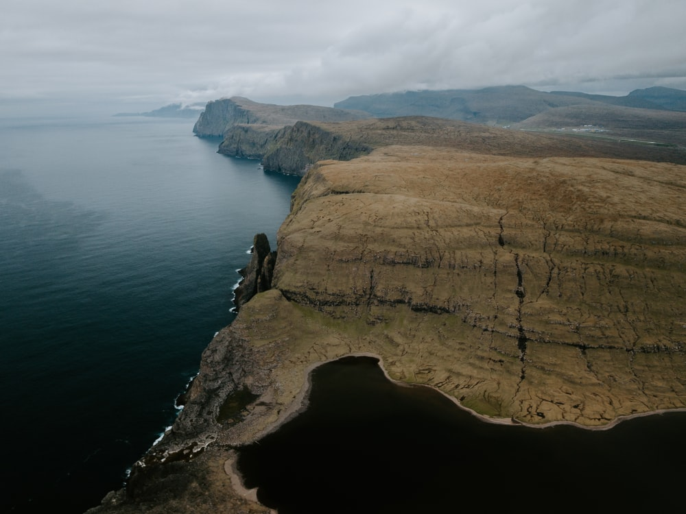 high angle photography of cliffs near body of water