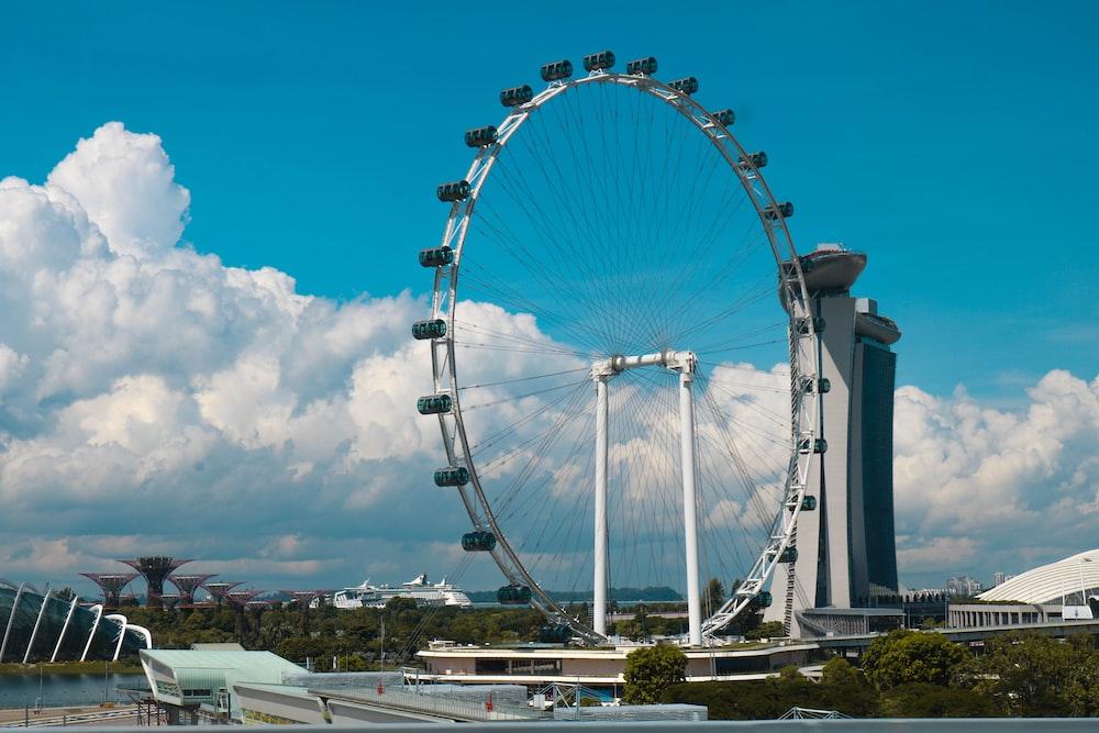 Ferris Wheel beside high-rise building during daytime