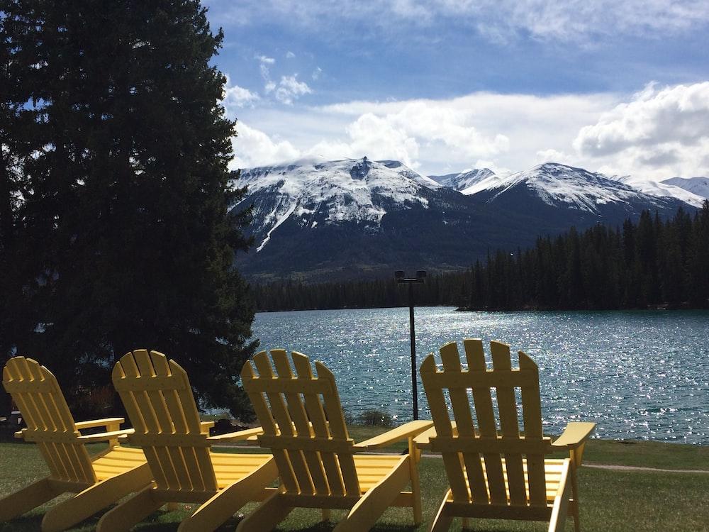 four yellow adirondack chairs near lake during daytime