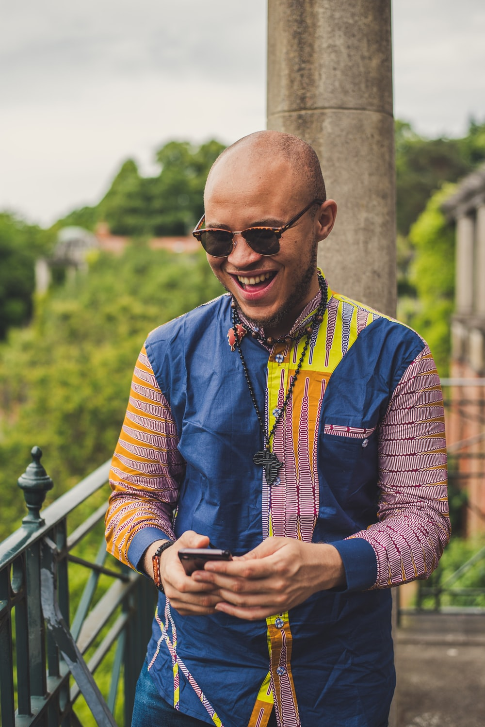 smiling man in multicolored dress shirt and brown sunglasses