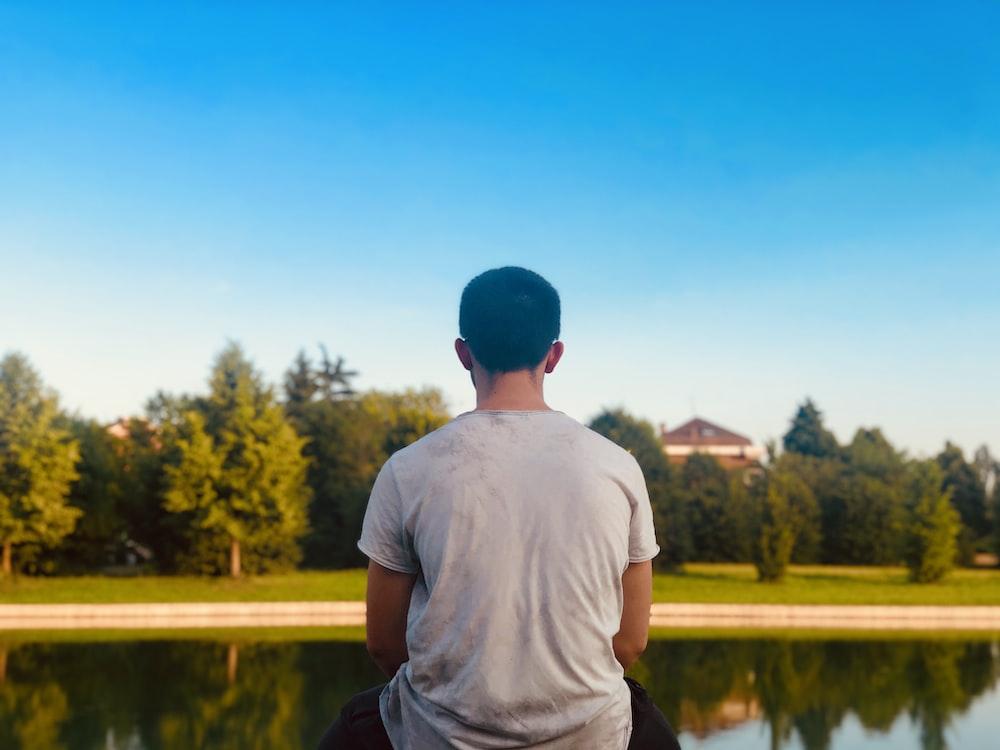 池に面して座っている白いシャツの男