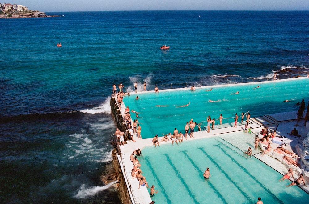 people gathering near swimming pool beside seashore during daytime