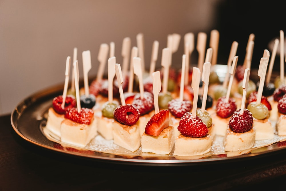 slice mini cakes with strawberry, raspberry, and blueberry on top