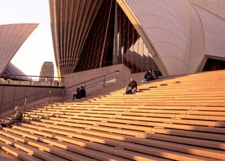 people sitting on bench on Sydney Opera House during daytime