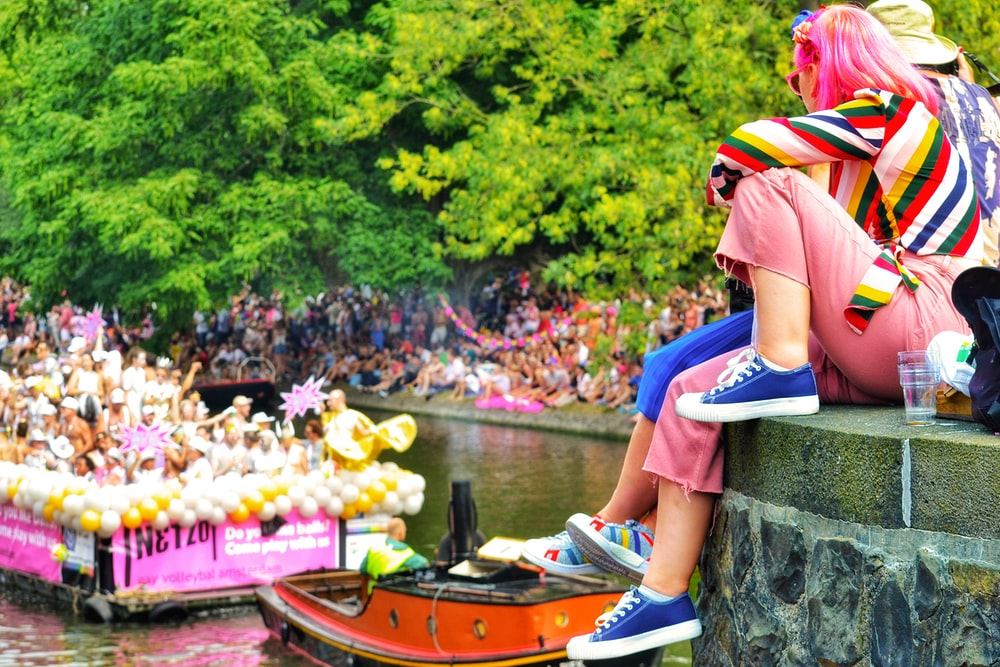 woman in multicolored shirt and pink pants sitting on docks watching boats in fluvial parade