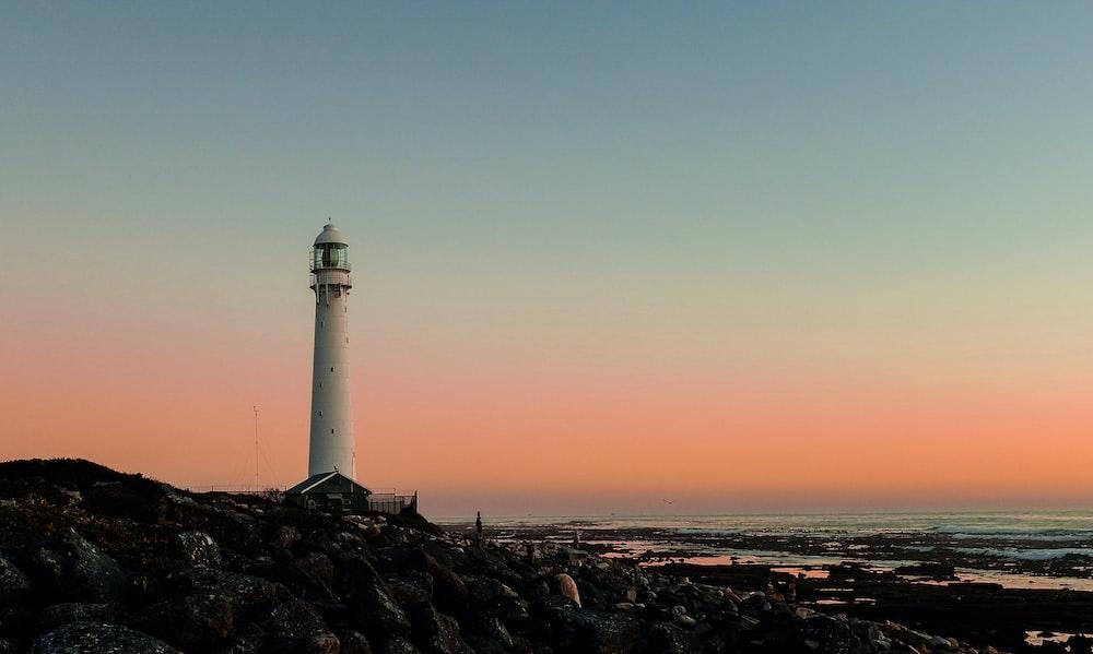 white lighthouse on hill in beach under orange sky at sunset