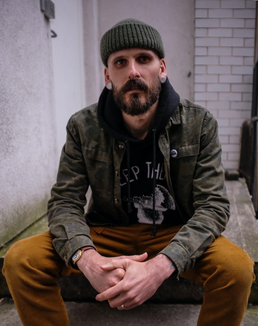 man wearing jacket seated near wall
