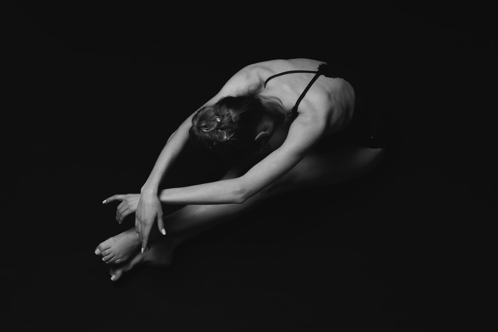 grayscale photography of unknown person stretching