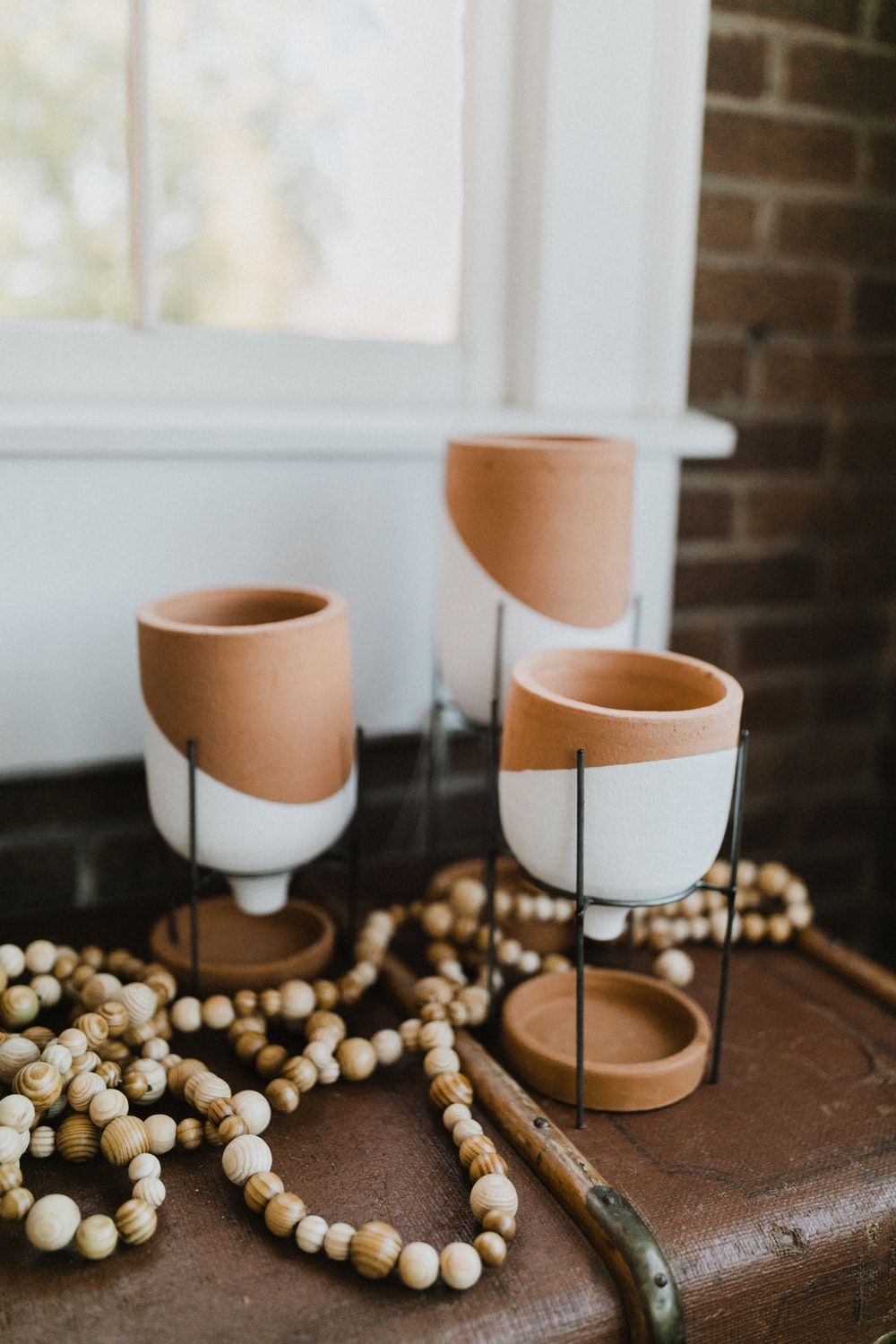 three white and brown ceramic candle holders on desk