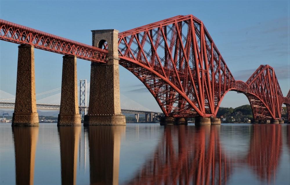 red metal bridge near white metal bridge during daytime