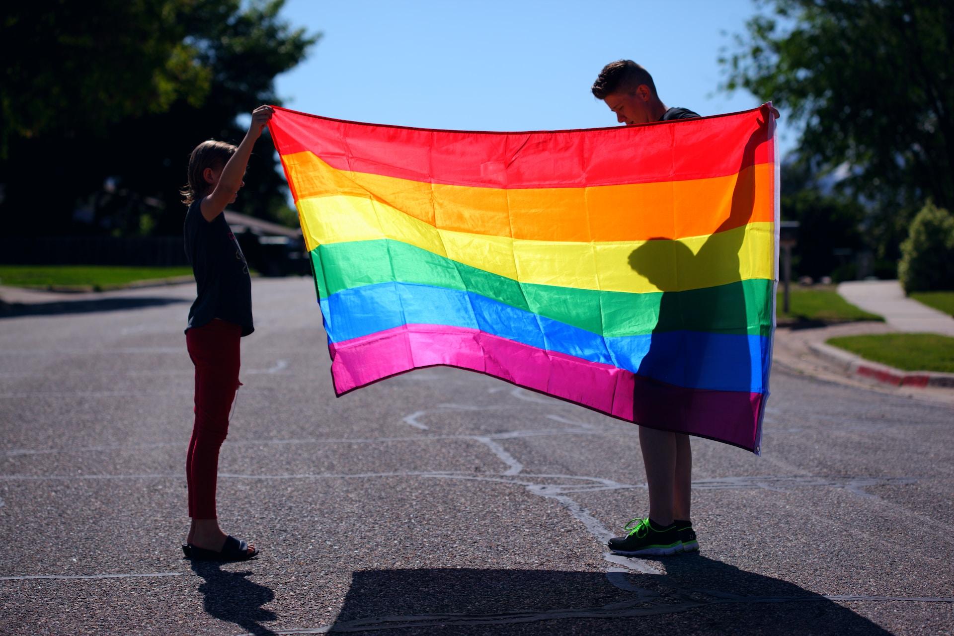 man and girl holding rainbow flag