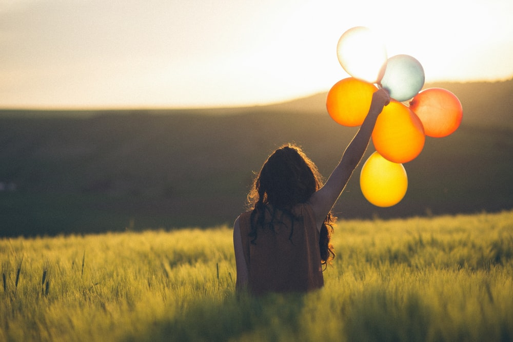 unknown person holding balloons outdoors