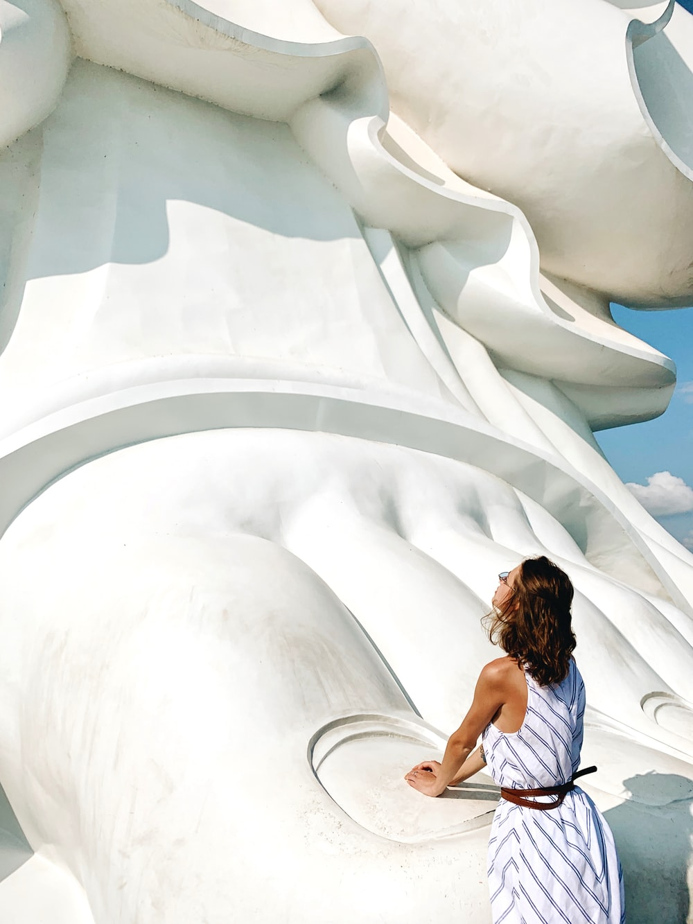 woman standing beside human foot monument during daytime