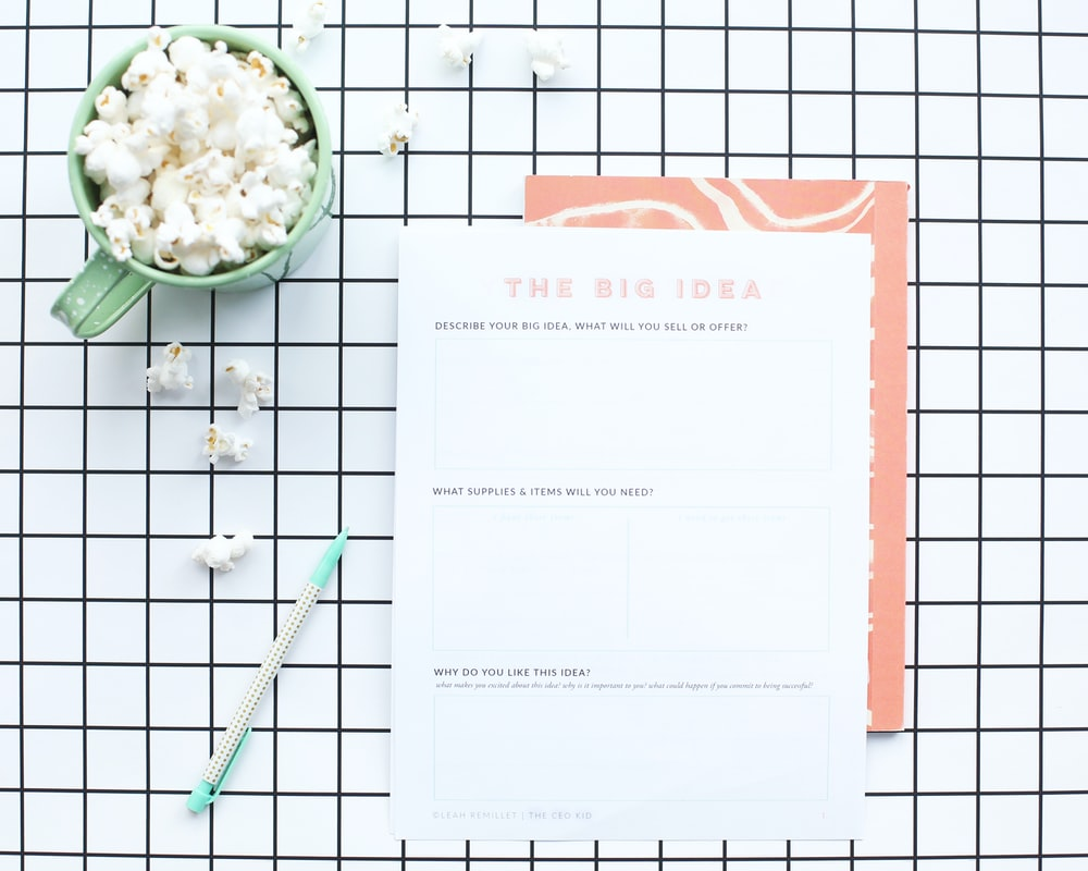 white printer paper near green ceramic mug