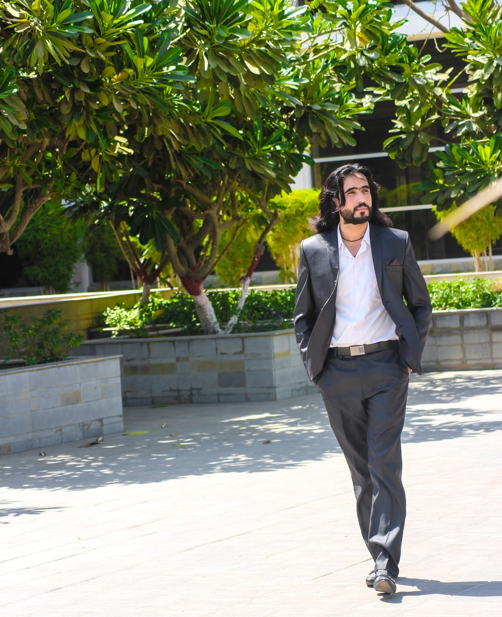 man in black suit jacket walking near trees
