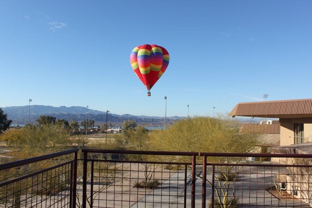 red, green, and blue hot air balloon flying near body of water during daytime