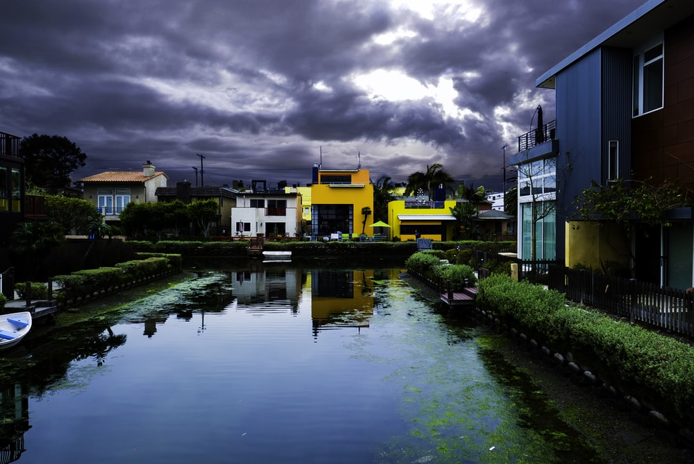 buildings near body of water under cloudy sky during daytime