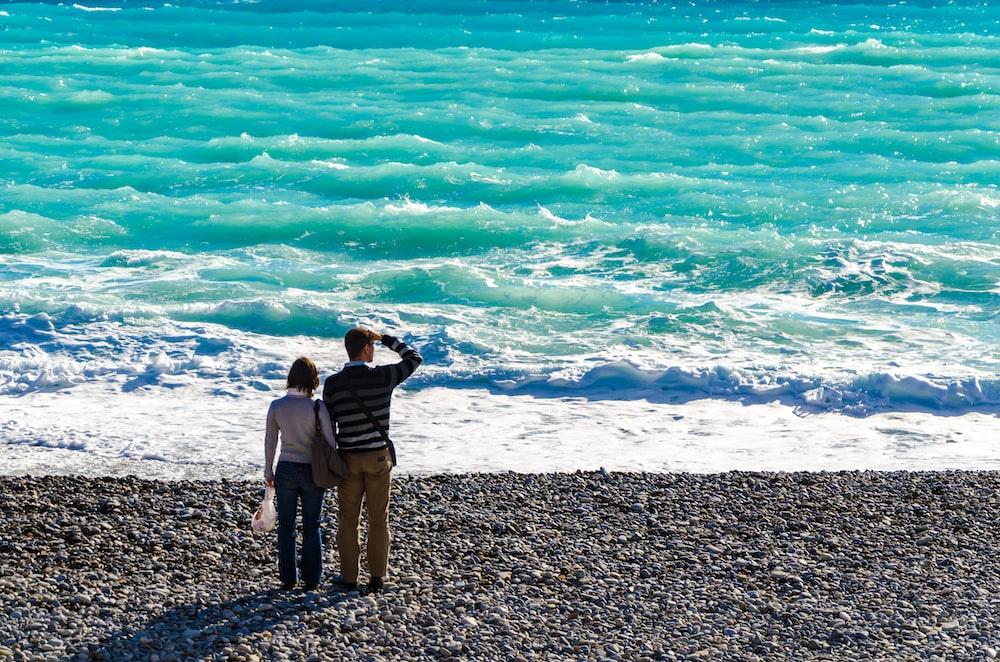man standing beside woman on shore