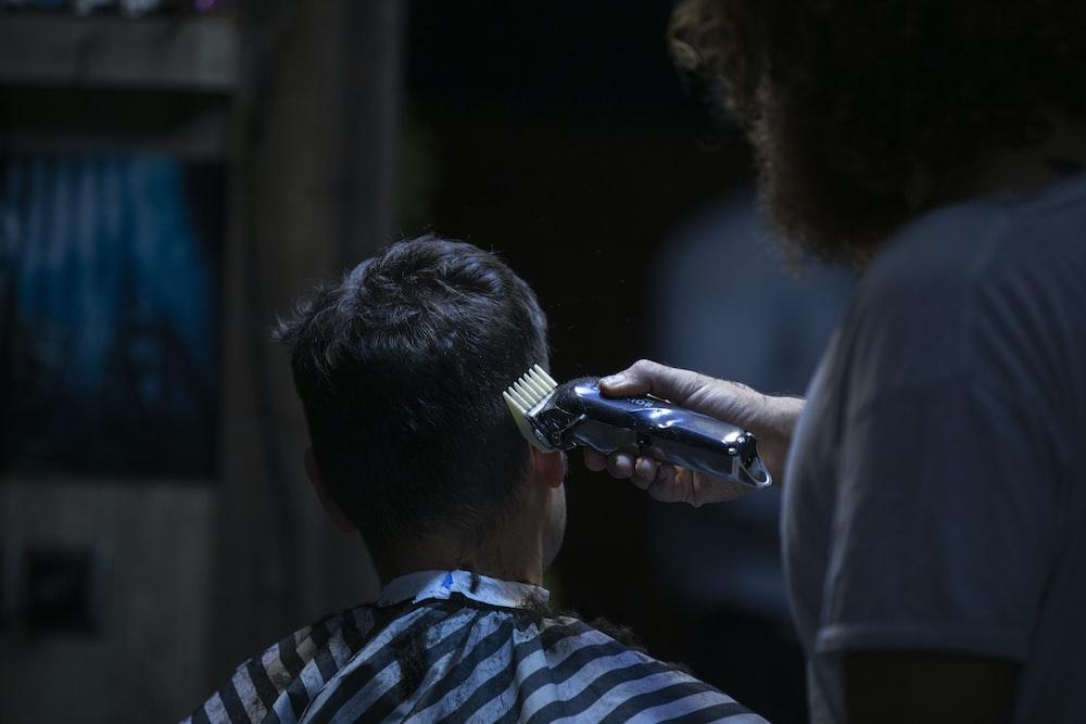 man cutting the hair using hair clipper photography