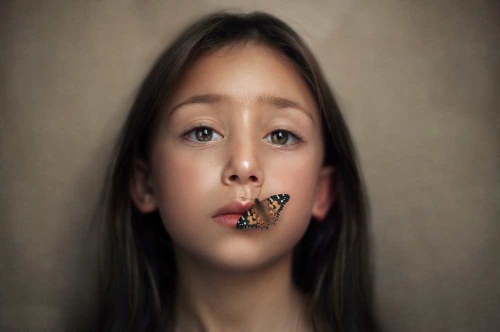 girl with butterfly perched on her lips