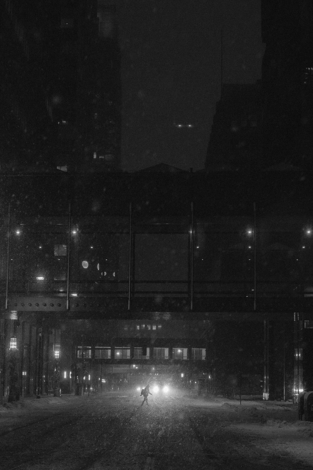 grayscale photography of walking person on road during night